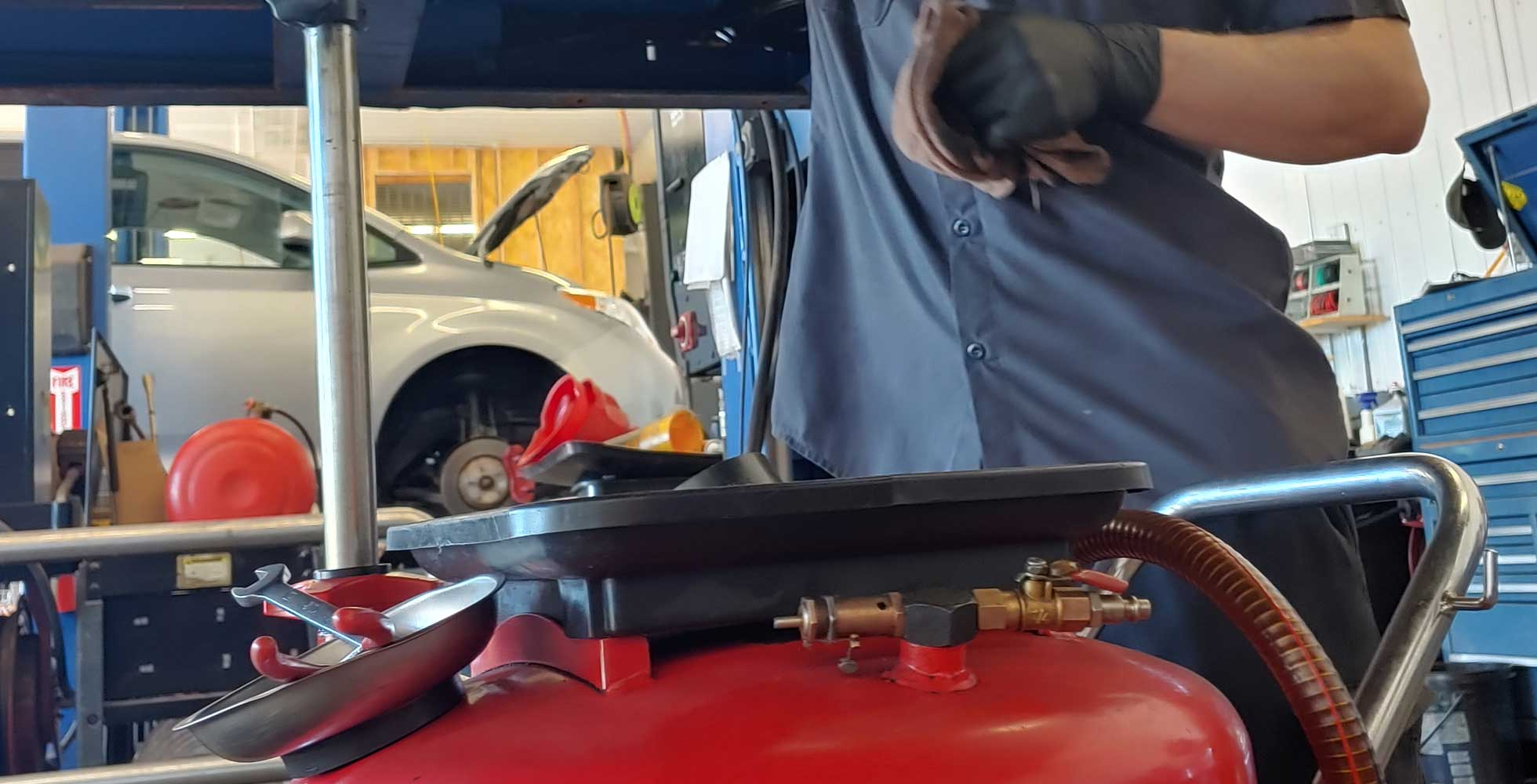 Paul's Auto Mechanic checks oil